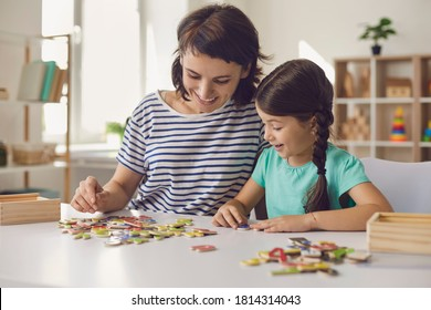 Happy young mother and smiling daughter sitting and collecting puzzle together at home with room interior at background. Happy childhood and motherhood concept