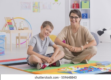 Happy young mother with son sitting on a floor