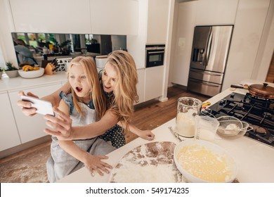Happy young mother taking selfie with her daughter in kitchen. Young woman and little girl making food in kitchen taking self portrait with mobile phone.