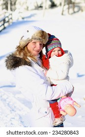 Happy young mother with toddler daughter in white warm jackets enjoying apres-ski during vacation in snowy alpine village