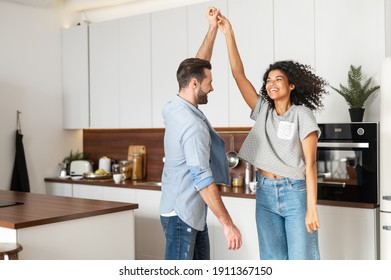 Happy young multi ethnic couple in love dancing and holding hands in the kitchen. Joyful boyfriend and girlfriend have a fun at home, newlywed moved in new apartment