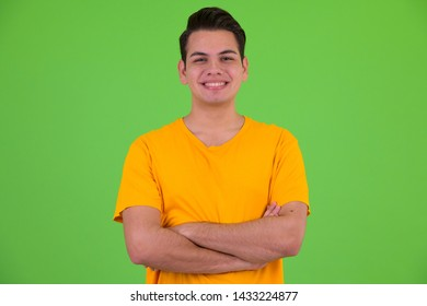 Happy young multi ethnic man smiling with arms crossed