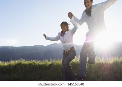 Happy young multiethnic couple jumping while holding hands in park