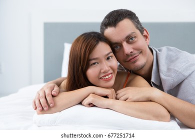 Happy young multiethnic couple lying in bed