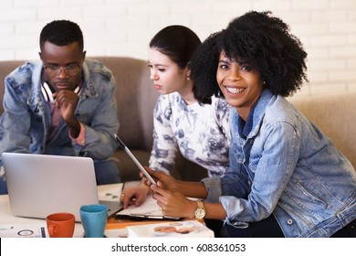 Happy young multiracial group of young university students studying with books and laptop in cafe. Group of multiracial people in college library study.