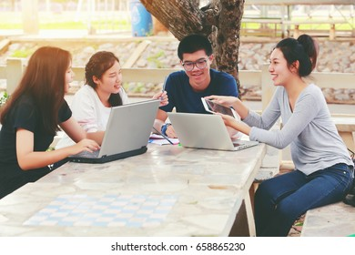 Happy young multiracial group of young university students studying with books and laptop outdoor. Mixed raced people sitting at table reading books for university assignment.