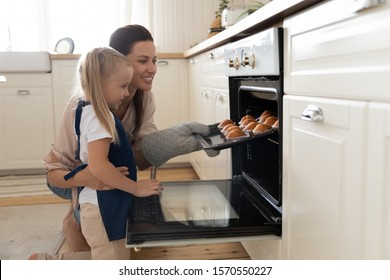 Happy young mum and cute kid daughter wear aprons bake muffins in kitchen, smiling mother teaching child take tray with cupcakes dessert make cakes out oven stove cook at home, family bakery concept