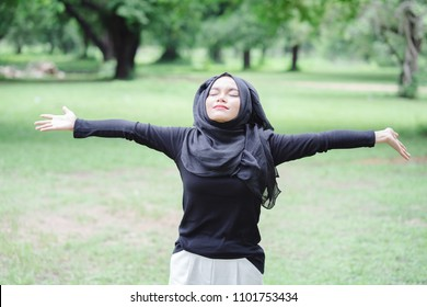 Happy young muslim asian woman doing exercise before running in the green park background. Healthy lifestyle and good wellness concepts.