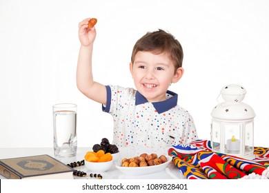 Happy young Muslim boy holding a date ready for iftar( breakfast ) in Ramadan