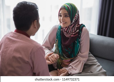 happy young muslim woman having a chat with her husband at living room