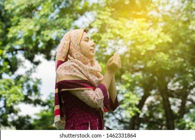 Happy young muslim woman with hijab dress praying for Allah, muslim God,Praying hands ,muslim meditating pray,muslim prayer