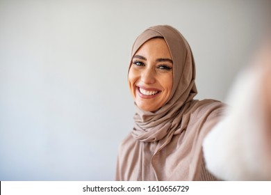 Happy young muslim woman take self portrait with handphone at home. Happy arab woman in hijab with mobile phone making selfie. Portrait of smiling girl, posing.