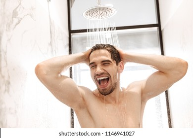 Happy young naked man having a shower