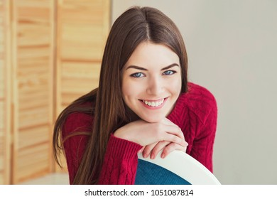 Happy young natural beauty woman with bright smile in red knitted pullover. Happy teen girl with long brown hair sitting on the chair in the room