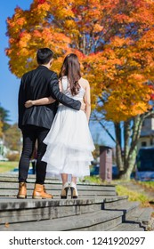 Happy young newly married wedding couple on walk in golden yellow fall autumn park in japan, Relationship love concept. Man woman on nature outdoors