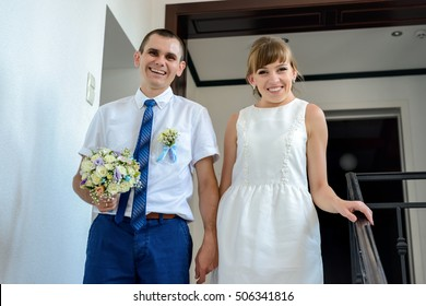 Happy young newlyweds leaving the bridal office pausing on the steps holding hands to smile at the camera