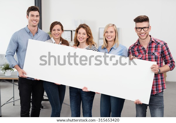 Happy Young Office Workers in Casual Outfits, Holding a Plain White Rectangular Poster with Copy Space and Smiling at the Camera.