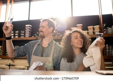 Happy young owners of cafe or restaurant standing by counter and cleaning glasses with towels at the end of working day