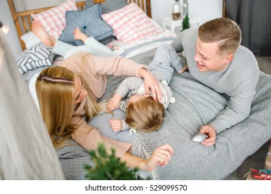 Happy young parents with baby boy on the bed in christmas decorated room
