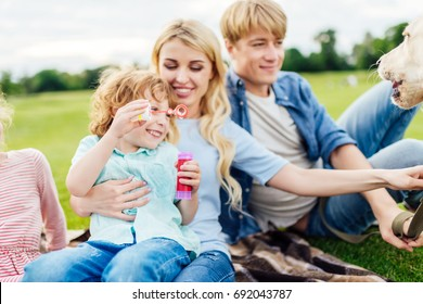 happy young parents with cute little son blowing soap bubbles together in park