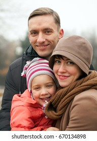 Happy young parents with   daughter  walking in   park in autumn.