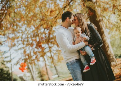 Happy young parents have fun with baby boy in autumn park