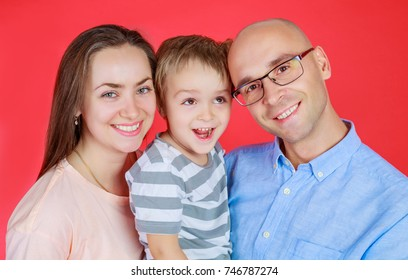 happy young parents with a little son isolated against red background