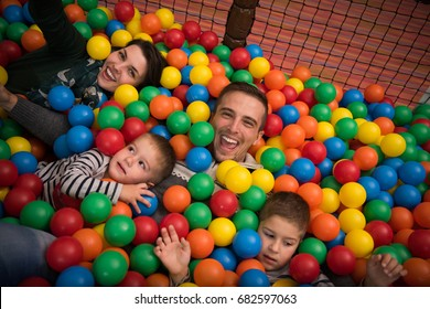 Happy young parents are playing with their kids at pool with colorful balls in a children's playroom