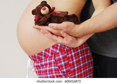 Happy young parents show toy of their future baby on background of big belly pregnant mother