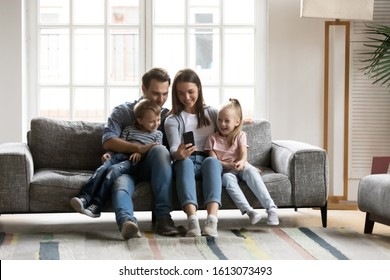 Happy young parents sit on couch with little children have fun using smartphone together, smiling caucasian family with small kids relax on sofa in living room watch funny videos on cellphone