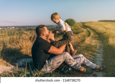 happy young parents sitting and carrying adorable little son in rural landscape