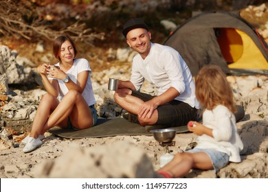 Happy young parents sitting on black ground pad near tent, drinking tea from iron cups and looking at little daughter sitting near and playing. Mom and dad smiling, enjoying vacation together.