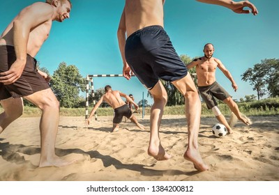 Happy young people in active dynamic action with ball funny play in football on the beach under sun light in summer time and in sunny day. Soccer on the sand.