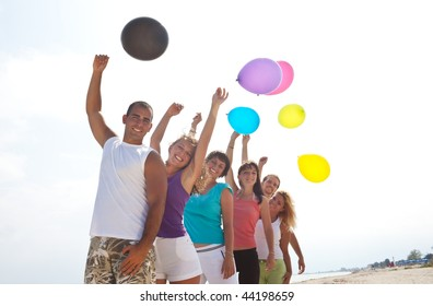 happy young people with balloons in nature