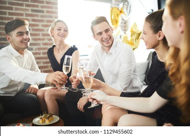 Happy young people with champagne gathered for home party for fun and talk