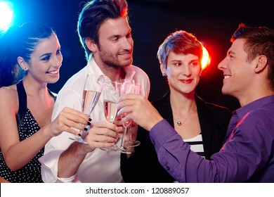 Happy young people clinking with champagne in nightclub.