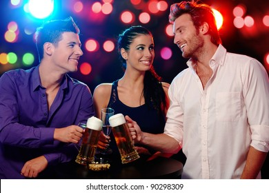 Happy young people clinking glasses at a party, smiling.?