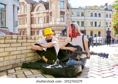 Happy young people couple guy and girl playing acoustic guitar. Trending creative teenagers sitting on sidewalk outside, in guitar case, small cash, hobbies leisure, adolescence, creativity lifestyle