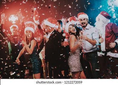 Happy Young People Dancing on New Year Party. Santa Claus. People in Red Caps. Happy New Year Concept. Glass of Champagne. Celebrating of New Year. Young Woman in Dress. Men in Suits.