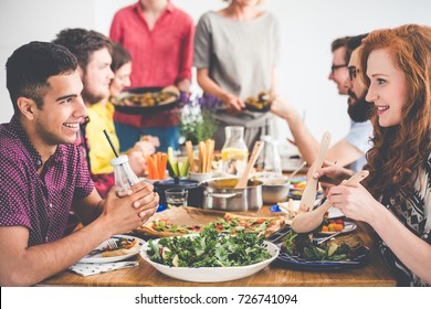 Happy young people eating fresh salad and falafel in the company of friends, multiracial couple at vegetarian party with catering