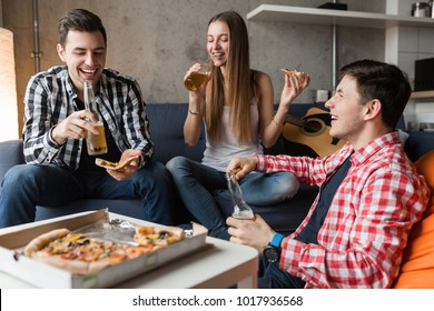 happy young people eating pizza, drinking beer, having fun, friends party at home, hipster company together, two men one woman, smiling, positive, relaxed, hang out, laughing