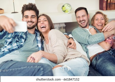 Happy young people enjoying time together sitting on sofa at home ,taking selfie.