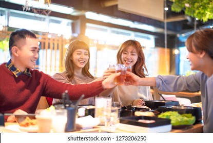 happy young people friends toasting and eating in the restaurant