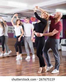 Happy young people having  rumba dancing class indoors