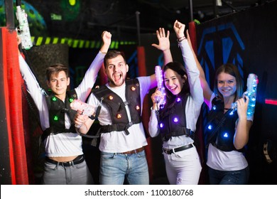 Happy young people with laser pistols posing together on dark laser tag labyrinth