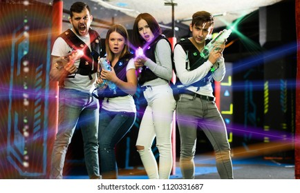 Happy young people with laser pistols posing together in bright beams in laser tag labyrinth