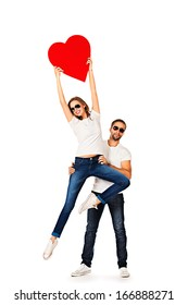 Happy young people in love posing with big red heart. Isolated over white.