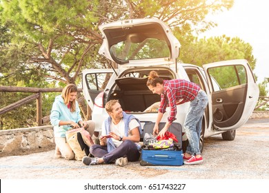 Happy young people pack their suitcase for a beautiful roadtrip holiday adventure with the car. Best friends chill and having fun making jokes about the travel trip. Concept af adventure and travel.