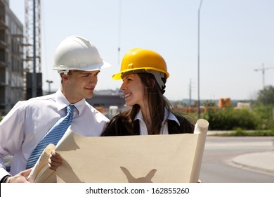Happy young people planing future house on construction site.