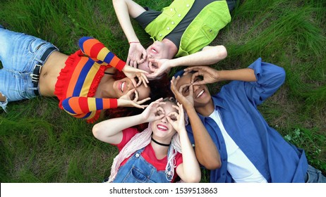 Happy young people showing ok gesture like binoculars lying campus park grass